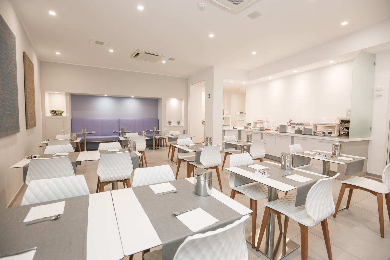 L'Hotel Executive Inn è una spaziosa e raffinata sala colazione con numerosi posti a sedere.