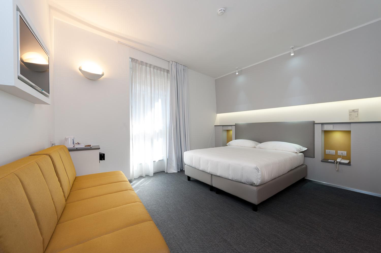 Hotel Executive Inn è una camera doppia deluxe con un letto bianco, una TV e un accento arancione con un divano.