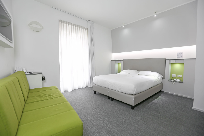 Hotel Executive Inn è una camera doppia deluxe con un letto bianco, TV e un accento verde con un divano.