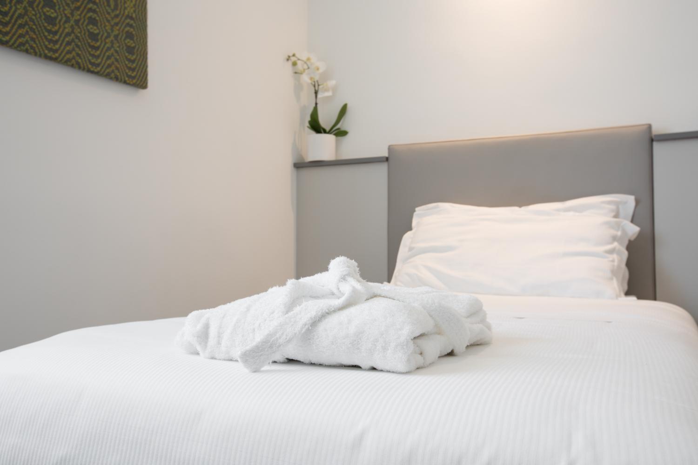 Hotel Executive Inn Camera singola standard, accappatoio bianco su un letto pulito