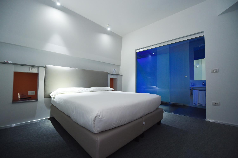 Hotel Executive Inn è una camera doppia standard, una vista generale dalla finestra a un interessante schema di colori usando i colori blu, bianco e arancione