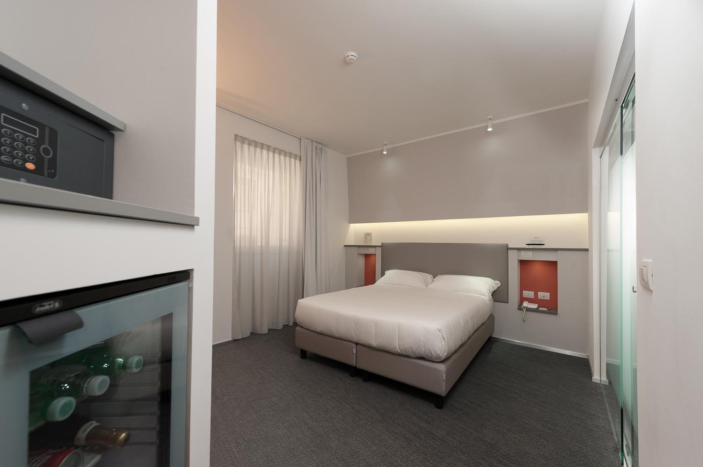 Hotel Executive Inn camera doppia standard, vista generale della finestra, cassaforte, minibar, accento arancione